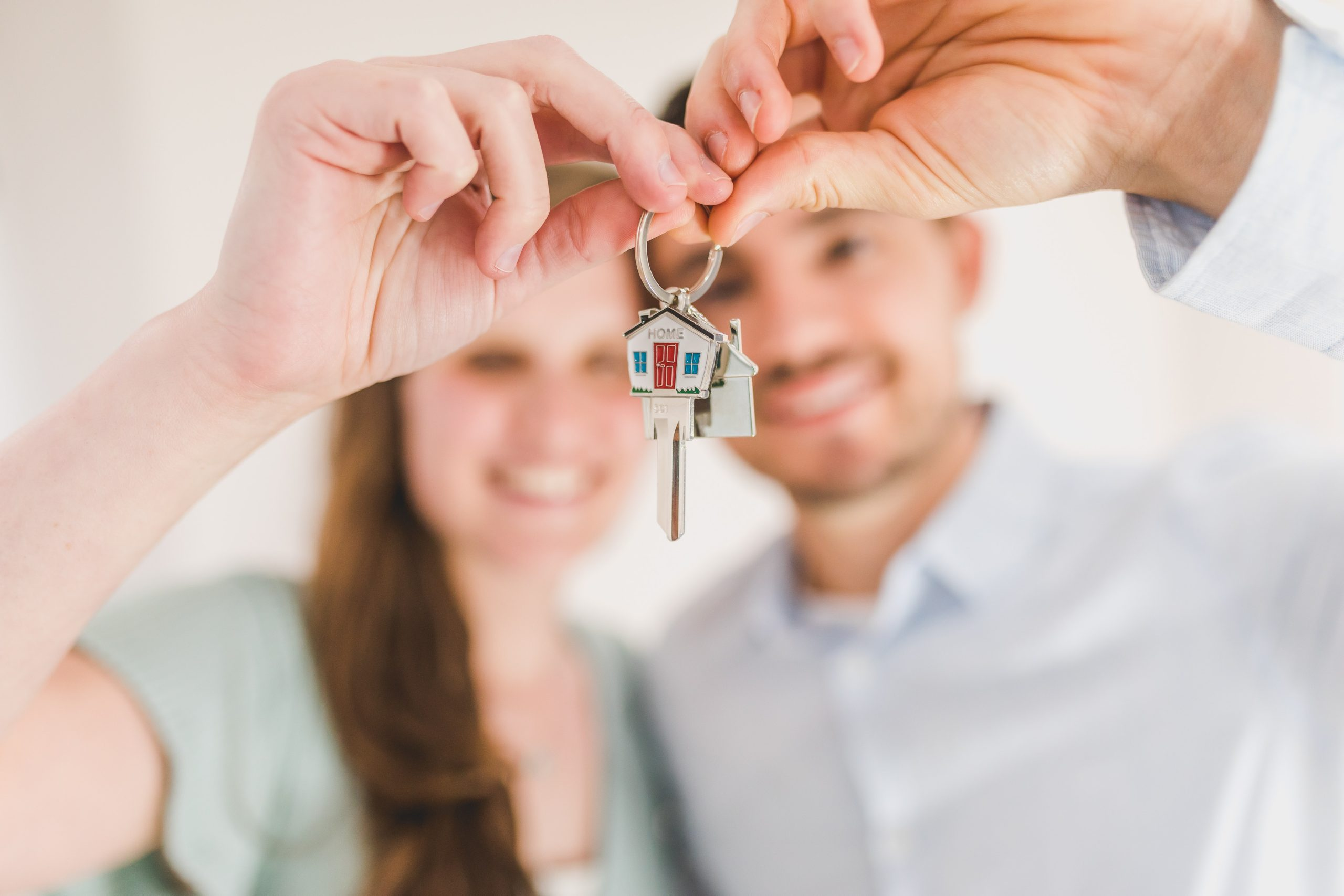 Man and woman holding keys to new home